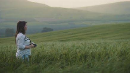 Thumbnail for Ein Mädchen Fotos iert Landschaft in der Mitte des Weizenfeldes bei Sonnenuntergang