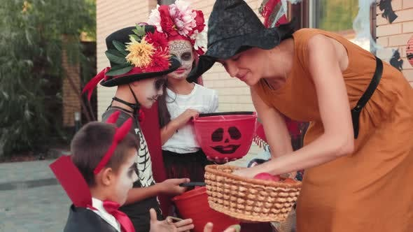 Adorable Children in Halloween Costumes Receiving Candy from Woman