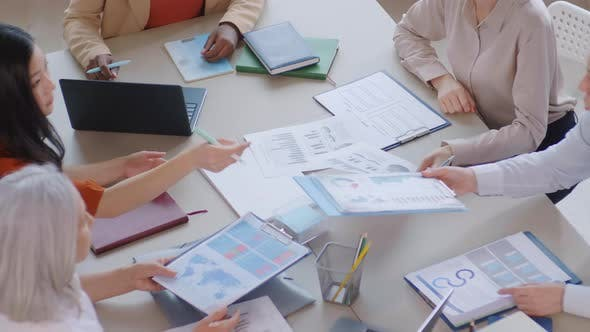 Group of Five Businesswomen Analyzing Charts