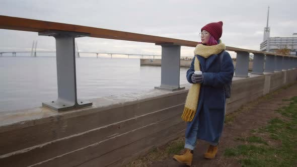 Thumbnail for Asian Woman Walking with Coffee Cup along Riverside