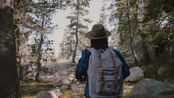 Thumbnail for Camera Follows Young Tourist Girl Hiking Alone with Backpack Up on Beautiful Rocks at Yosemite