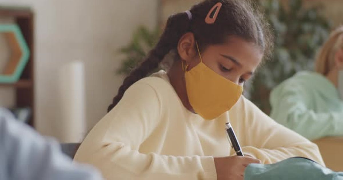 Black Schoolgirl in Face Mask Writing at Desk and Looking at Camera