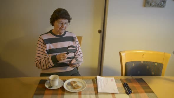 Senior Woman Reading Paper with Magnifying Glass in the Dining Room