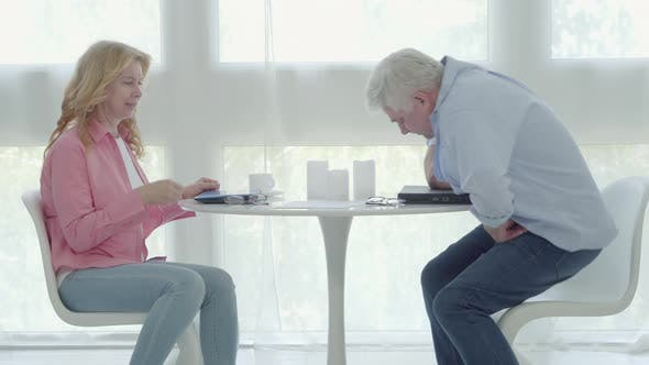 Sleepy Mid-adult Man and Woman Sitting at the Table in the Morning, Putting on Eyeglasses and