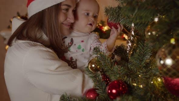 Baby in Mama Arme auf Weihnachtsnacht am Baum