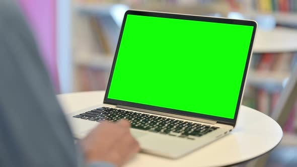 Man Using Laptop with Green Chroma Key Screen Rear View
