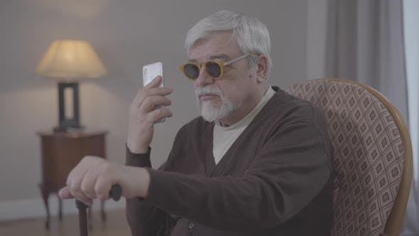 Thumbnail for Portrait of Blind Old Caucasian Man Talking on the Phone Indoors. Grey-haired Male Retiree in