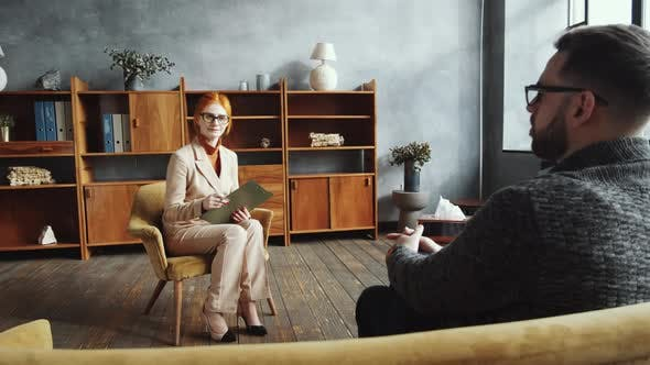 Middle-Aged Female Counselor Listening to Male Patient