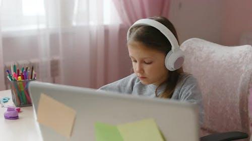 Schulmädchen studiert online auf Laptop zu Hause