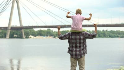 Dad With Son on His Shoulders Looking at City, Showing Strength and Confidence