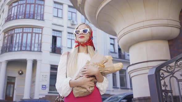 Cover Image for Portrait of Pretty Young Woman Standing on the Street Holding Freshly Baked Bread and Croissant