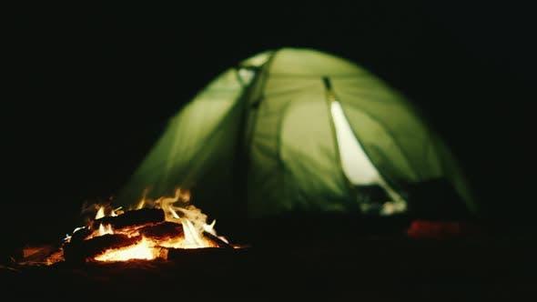Thumbnail for Das Zelt, in dem das Licht in der Nähe des Feuers leuchtet. Romantik und Entspannung in der Natur
