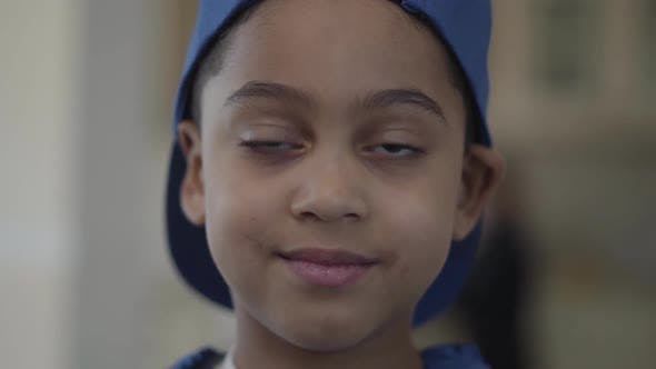 Thumbnail for Face of an African American Boy in a Blue Cap Looking Into the Camera
