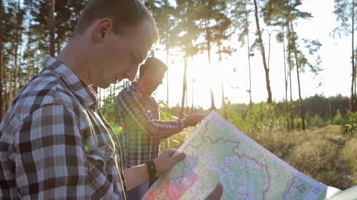 Travelers with a map and a compass in their hands are looking for their way. Terrain orientation.