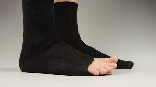 Side view of socks with a hole on the man's legs