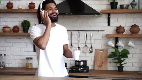 Young attractive African man listens to music and dances using white headphones