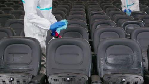 Arbeiter reinigen Stühle mit Desinfektionsmitteln im Kino