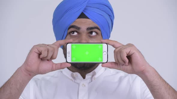 Thumbnail for Face of Happy Young Bearded Indian Sikh Man Thinking While Showing Phone