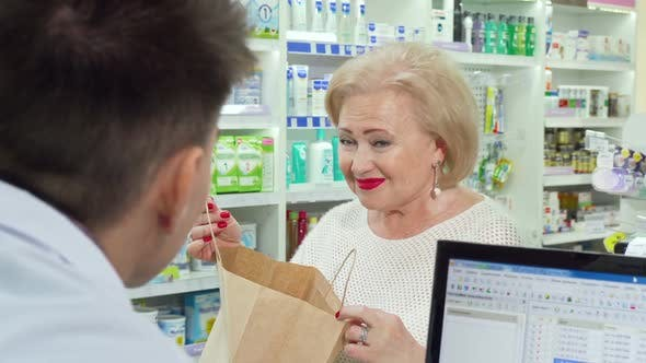 Thumbnail for Senior Woman Buying Medical Products at Pharmacy, Looking in a Shopping Bag