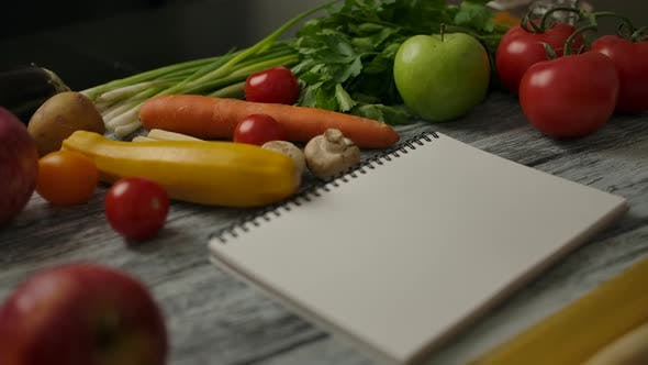 Thumbnail for Blank Notepad for Recipe Amidst Vegan Food on Table