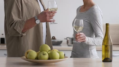 Couple Clinking Glasses Drinking White Wine In Kitchen Indoor Cropped
