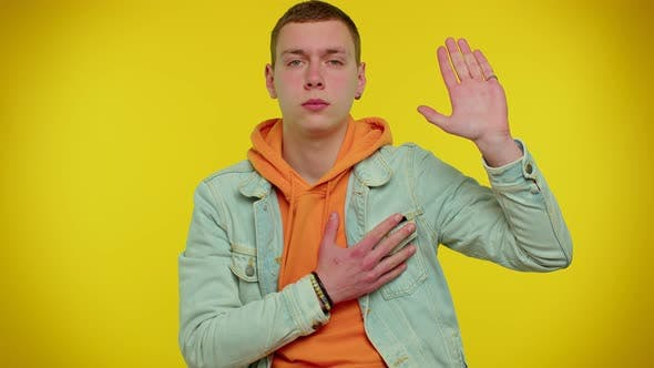 Sincere Responsible Teen Man Raising Hand to Take Oath Promising to Be Honest and to Tell Truth