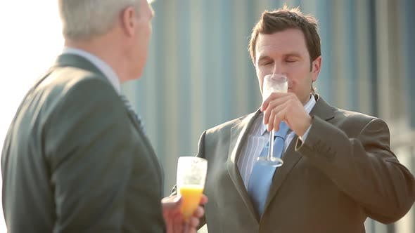 Businessmen talking and toasting with bucks fizz
