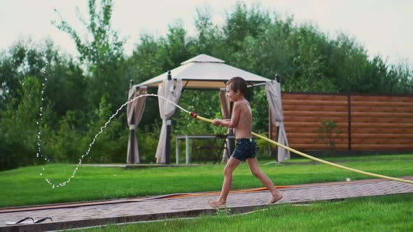 The Two Boys Are Playing with Mom and Dad in the Backyard of Their House Drenching with Hose
