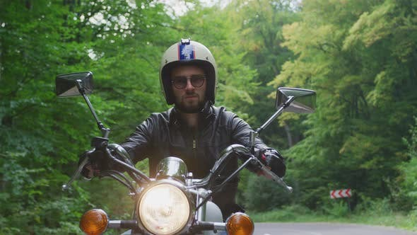 Thumbnail for Man riding a motorcycle on a forest road
