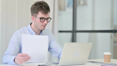 Man with Laptop Reading Documents in Office