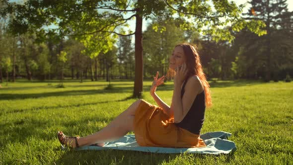 Thumbnail for Happy Female Sitting on Green Grass and Have Conversation Via Digital Smartphone Device