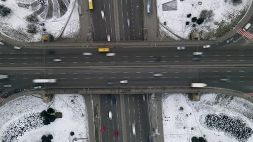 Aerial timelapse of the cars passing by on a highway and a bridge at winter