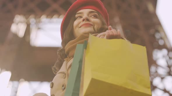 Thumbnail for Happy brunette girl holding purchases, looking for mall, successful shopping