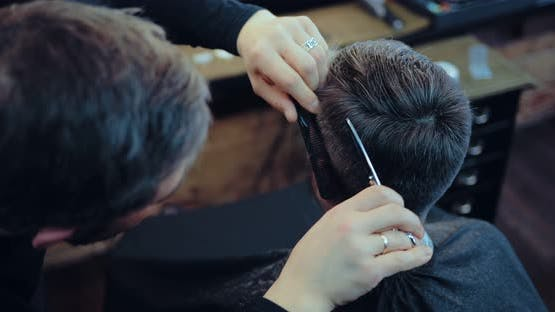 Professional Hairdresser Does a Haircut to a Man in the Salon