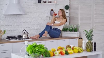 Beautiful model drinking juice on the kitchen table. Young woman in jeans sitting on the table
