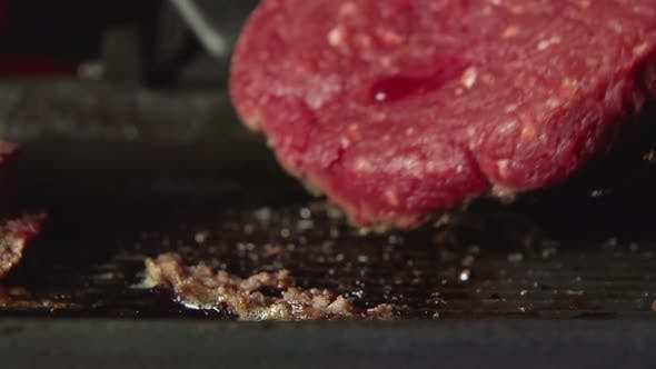 Thumbnail for A cook turns over a blood beefsteak on a grill