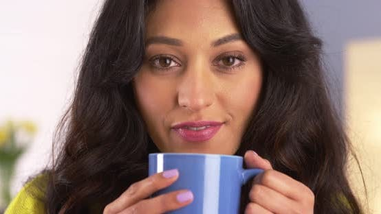 Happy Mexican woman holding mug