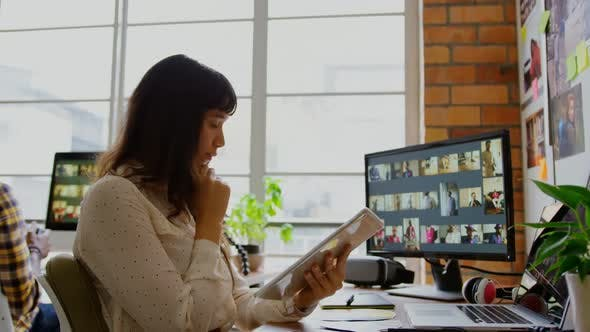 Female graphic designer using digital tablet in a modern office 4k