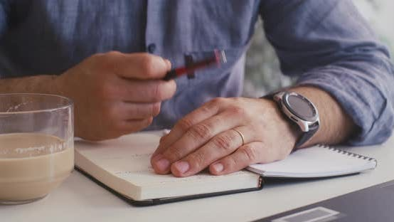 Cover Image for Man Taking Notes in a Notebook