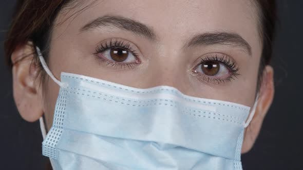 Girl with pretty eyes wearing face mask looking at the camera