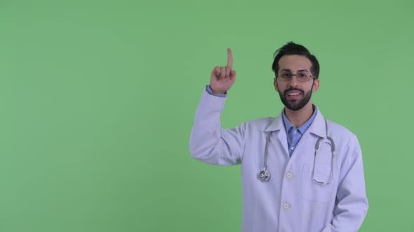 Thumbnail for Happy Young Bearded Persian Man Doctor Talking and Pointing Up