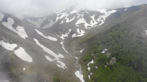 Aerial Forested Mountain With Snow Fragments Among The Clouds in The Spring