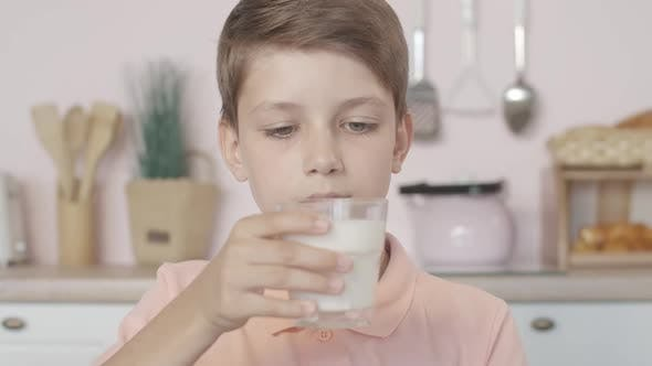 Close-up of Mischievous Little Boy Smelling Milk in Glass with Dissatisfied Facial Expression
