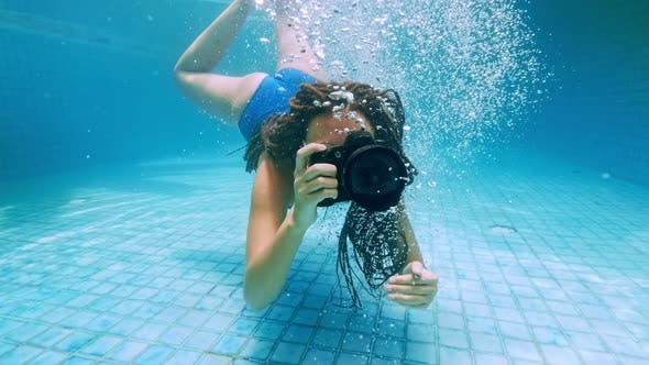 Cover Image for Travelling Girl in Asia. Happy Young Woman with Beautiful Long Hair Swim Under Water with Camera in