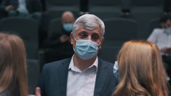 People in Medical Masks Chatting at a Conference