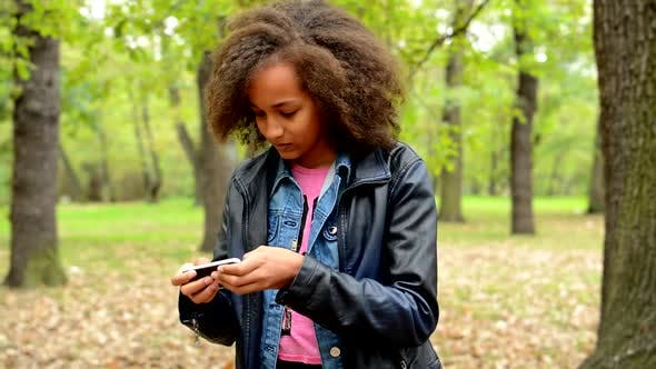 Thumbnail for Young Beautiful Playful African Girl Plays Motion Games on the Smartphone in the Park