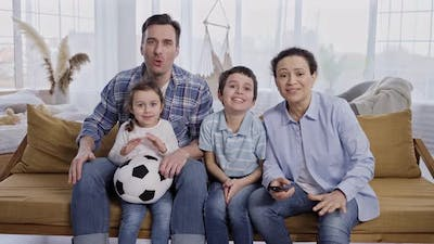 Family of Football Fans Watching Match on TV