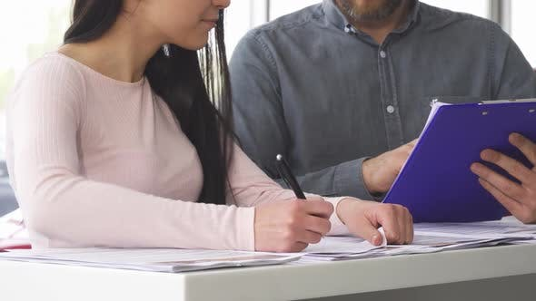 Thumbnail for Cropped Shot of a Woman Signing Papers with the Salesman at the Car Salon