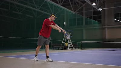 Beginning Tennis Player is Learning to Serve Fulllength Portrait on Indoor Tennis Court Training and