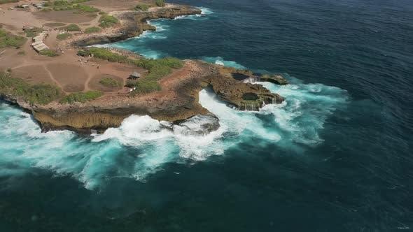 Thumbnail for Aerial view flying over huge ocean waves breaking against cliffs